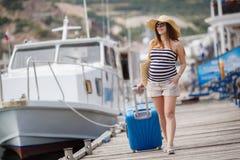 码头的怀孕的美丽的妇女在海 免版税库存图片