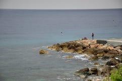 码头的渔夫由海 库存图片