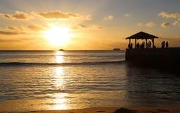 码头等待的日落的人们 免版税库存图片
