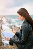 码头观看的地图的妇女 库存照片