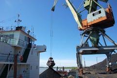 码头边货物起重机装载煤炭在内河港Kolyma 库存图片