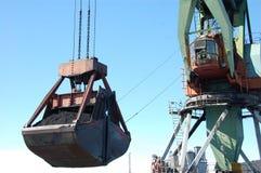 码头边货物起重机装载煤炭在内河港Kolyma 图库摄影