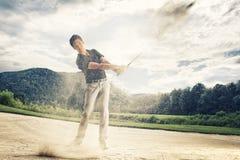 砂槽的高尔夫球运动员。 免版税库存照片