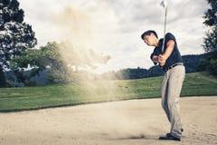 砂槽的高尔夫球运动员。 库存照片