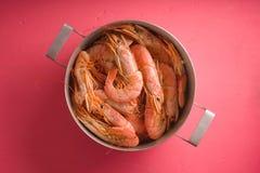砂锅用在一张明亮的桃红色桌上的虾 库存照片