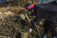 砍与一个轴的美丽的年轻女人木柴在村庄在冬天期间加热房子 免版税图库摄影
