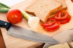砍刀子蔬菜的董事会面包 图库摄影