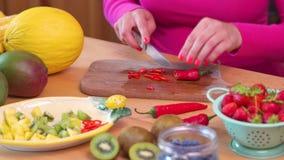 砍在桌上的一件桃红色女衬衫的妇女辣红色辣椒 影视素材