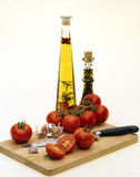 砍大蒜油橄榄蕃茄的董事会 免版税库存照片