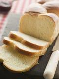 砍大面包的董事会奶油蛋卷切 免版税图库摄影
