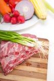 砍新鲜的猪排和菜 免版税库存照片