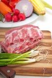 砍新鲜的猪排和菜 免版税库存图片