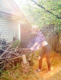 砍木头的严肃的妇女 库存照片