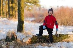 砍木头的男孩在自然的冬天 免版税库存图片