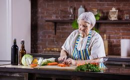 砍沙拉的资深妇女新鲜蔬菜 免版税图库摄影