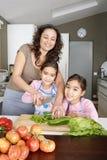砍素食者的妈咪和女儿 免版税图库摄影