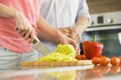砍菜的妇女的中央部位在有站立在背景中的人的厨房里 免版税库存照片