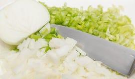 砍葱和芹菜与刀子 免版税库存图片