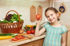 砍蕃茄、菜和新鲜水果的女孩在内部的厨房,健康食物概念里 免版税库存照片