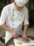 砍蘑菇的主厨 免版税库存照片