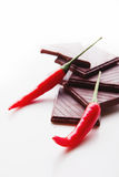 砍黑暗的巧克力用精选新鲜的炽热的辣椒 免版税库存图片