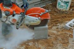 研磨机工作者剪切一块石头电工具 免版税图库摄影