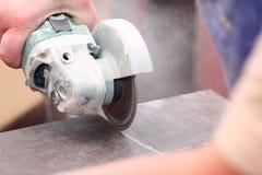 研磨机工作者剪切一块石头电工具 免版税库存照片