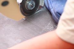 研磨机工作者剪切一块石头电工具 免版税库存图片