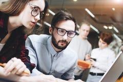研究一个新的项目的Coworking队 在木桌上的当代笔记本在一个现代顶楼办公室 库存图片