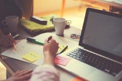 研究一个项目的两名妇女在办公室 膝上型计算机和文书工作在桌上 免版税库存照片