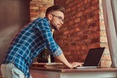 研究一台便携式计算机的法绒衬衣的英俊的学生在有顶楼内部的一间屋子里 免版税图库摄影
