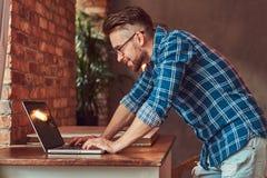 研究一台便携式计算机的法绒衬衣的英俊的学生在有顶楼内部的一间屋子里 免版税库存照片
