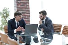研究一台膝上型计算机的两个商人在办公室 库存图片
