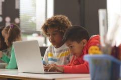 研究一台膝上型计算机的两个学校孩子正面图在教室 免版税图库摄影