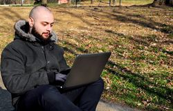 研究一台膝上型计算机的人在公园 免版税库存照片