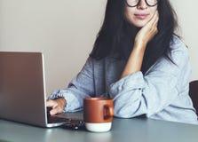研究一台膝上型计算机的妇女在她的家 库存图片