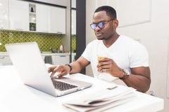 研究一台膝上型计算机的年轻非裔美国人的商人在现代内部的厨房里 库存图片
