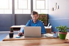 研究一台膝上型计算机的成熟商人在办公室 免版税库存图片