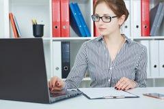 研究一台膝上型计算机的美丽的年轻女实业家在办公室 免版税库存照片