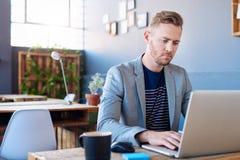 研究一台膝上型计算机的被聚焦的年轻商人在办公室 免版税库存图片