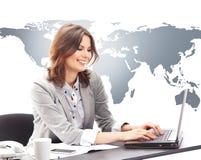 研究一台膝上型计算机的年轻女实业家在办公室 免版税库存图片