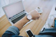 研究一台macbook或膝上型计算机的年轻人在咖啡馆 免版税库存图片
