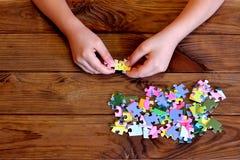 研究七巧板的孩子 孩子在手上的举行一个难题 小组在木桌上的七巧板 免版税图库摄影