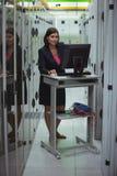 研究个人计算机的技术员,当分析服务器时 图库摄影