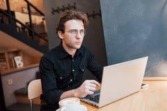 研究他的便携式计算机的创造性的人设计师,当等待对命令在他喜爱的咖啡馆户内,男学生时 免版税库存图片