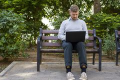 研究他的膝上型计算机的一位年轻行家自由职业者的画象坐一条长凳在公园 免版税图库摄影