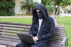 研究他的膝上型计算机的年轻黑客坐一条长凳在公园 免版税库存图片
