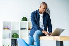 研究他的膝上型计算机的非裔美国人的商人的图象 他的书桌的英俊的年轻人 图库摄影