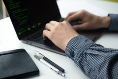 研究他的计算机的人 有膝上型计算机的人的手在白色桌上 免版税库存照片