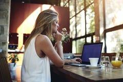 研究便携式计算机的一名年轻美丽的妇女的画象,当坐在现代咖啡馆酒吧内部时 库存照片